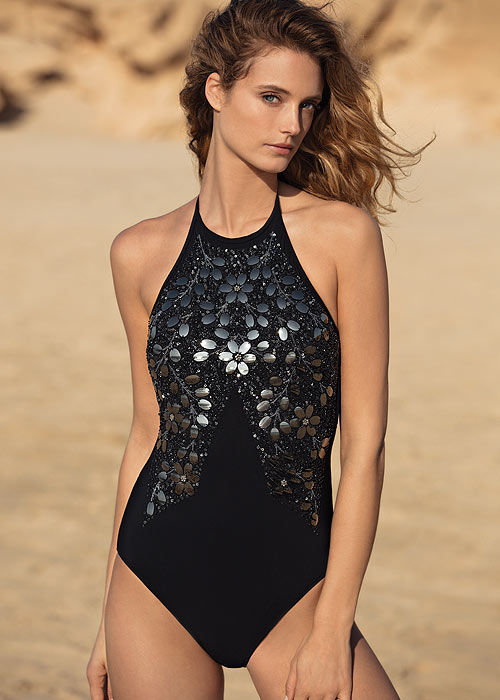 A beautifully patterned swimsuit design from Gottex. A simple black swimsuit decorated with an intricate floral pattern created from black mirrored sequins