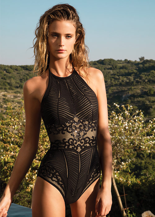 A subtle but striking swimwear design from Gottex. A high neck swimsuit in fine black mesh overlayed with intricately laser cut fabric decorated with black sequins.